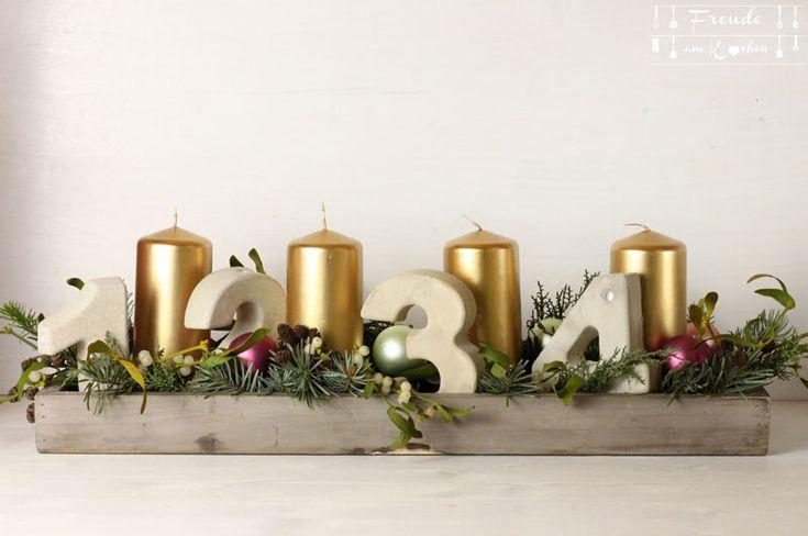 So schaut der Freude am Kochen Adventkranz aus. Dank einer Freundin ganz stylish mit Beton-Zahlen. Die Kombination mit den goldenen Kerzen gefällt mir.