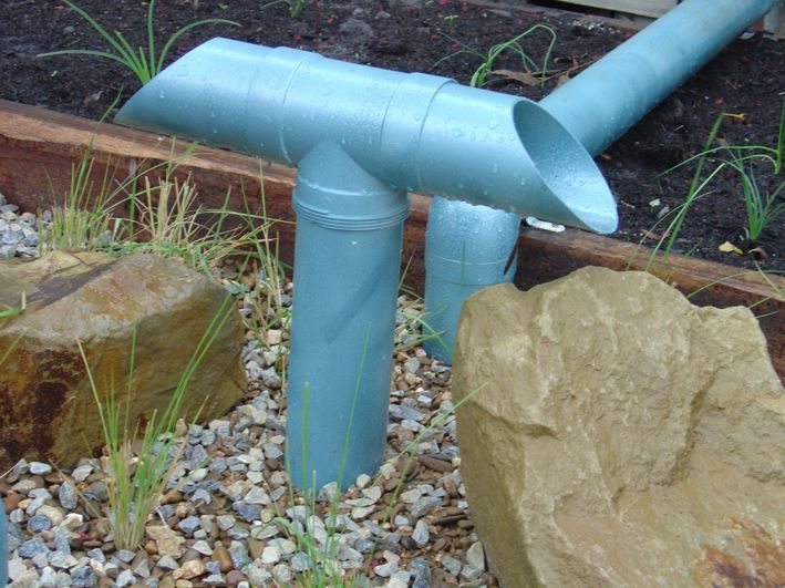Armadale Primary School Raingarden. Bright blue spreader creating striking colour contrast, while distributing rainwater onto the rocks.  The rocks help to prevent erosion of the filtration media.