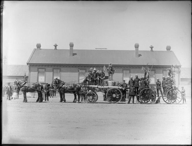 Christchurch Railways Volunteer Fire Brigade [float?], unidentified men in dress uniforms, hats and medals, horse drawn wagons carrying fire fighting equipment decorated in foliage, Railways depot behind