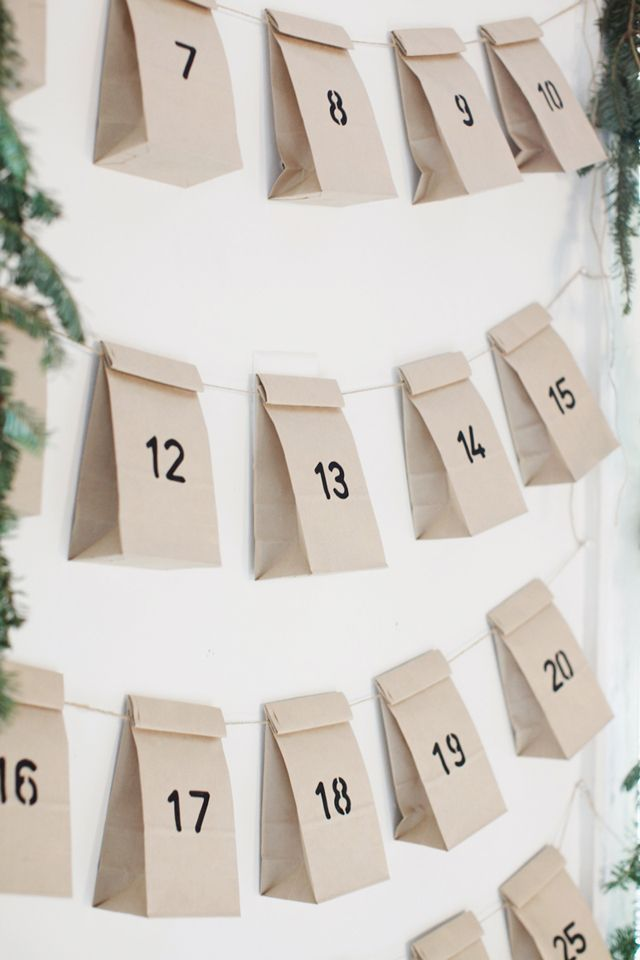 Simple Advent calendar made from brown paper bags, stenciled numbers, and a hanging garland for a pop of festive greenery.