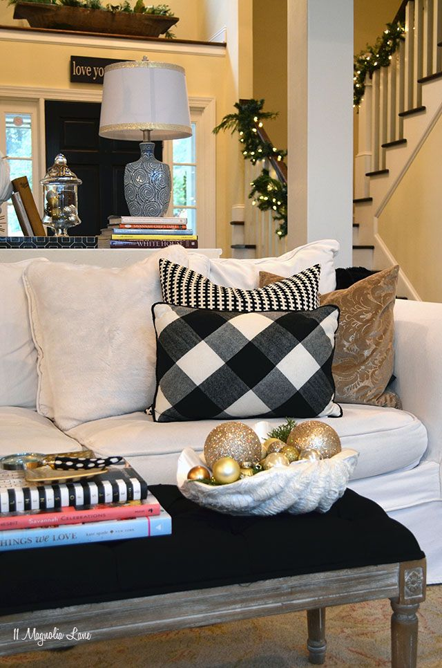 A white slipcovered sofa is the perfect neutral palette; just mix and match throw pillows and blankets to change your look for every season.  For Christmas we shopped HomeGoods for gold and faux fur pillows and created a holiday palette of black plaid, white, and gold. The tufted bench doubles as a coffee table or extra seating when hosting holiday parties.  {Sponsored by HomeGoods}