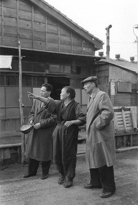 Undated vintage black and white photograph. Woman pointing, and two men. Japan.