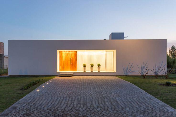 VISMARACORSI ARQUITECTOS の モダンな 家 シンプルな外観は、夜間にその美しさを最大限に表現することができます。その良い例をアルゼンチンからご紹介しましょう。真っ白い箱のような住宅には、くり抜かれたような正面玄関が設けられています。室内に明かりが灯るとその部分が立体的にに浮かび上がります。シンプルな形だからこそできる演出効果ですね。