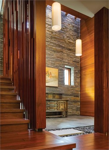The entry hall and stair feature a warm, organic material palette.