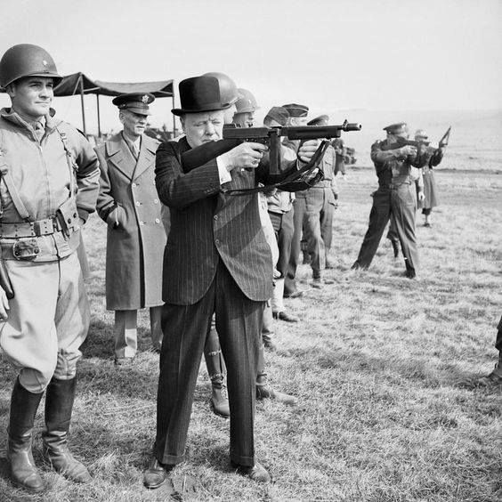 "Shortly before the Normandy invasion Winston Churchill tests his hand with the Thompson sub-machine gun in .45 caliber. The ""Tommy Gun"" was by then the standard light automatic weapon of the US Army and in extensive use by the British and Canadian armies. In the background General Eisenhower also takes aim with the same gun."