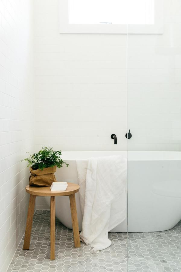 Marble hex tile, white tub and subway tile, and black fixture complemented with natural wood.