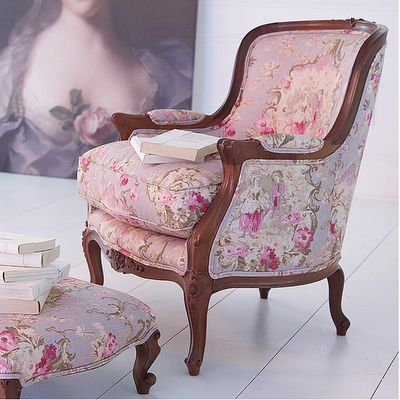 ahh i love the chair, the footstool...the upholstery, the books , the painting in the background...love it.