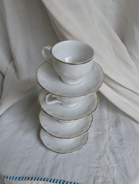 A set of delightful Antique German Coffee cups, White and Gold espresso time!  What cool little cups, demi tasse with style! a pleasant gold ring round the top...and they have a beautiful intricate pattern within the glaze...  They measure: 6.5cm wide by 6cm tall  There are a few flaws, due to their lovely age!.: one cup has a hairline crack, in the glaze, barely visible.. another cup a tiny chip in the rim... a tiny chip from the bottom of one handle... some wear on the gold…