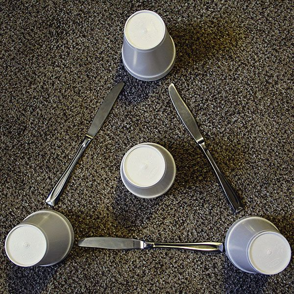 Fun LDS Object Lesson. Keeping the Commandments: Your goal is to use the three knives and the fourth cup to help a toy reach an invisible flag that is one stacked cup above the center of the triangle. Rules: You can move the knives but you can't move the three cups making the triangle.