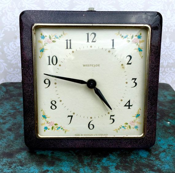 A very pretty Wesclox Alarm clock made in Scotland Circa 1950s. It has a purple enamel casing and a flower pattern on the face of the clock. In good working order.