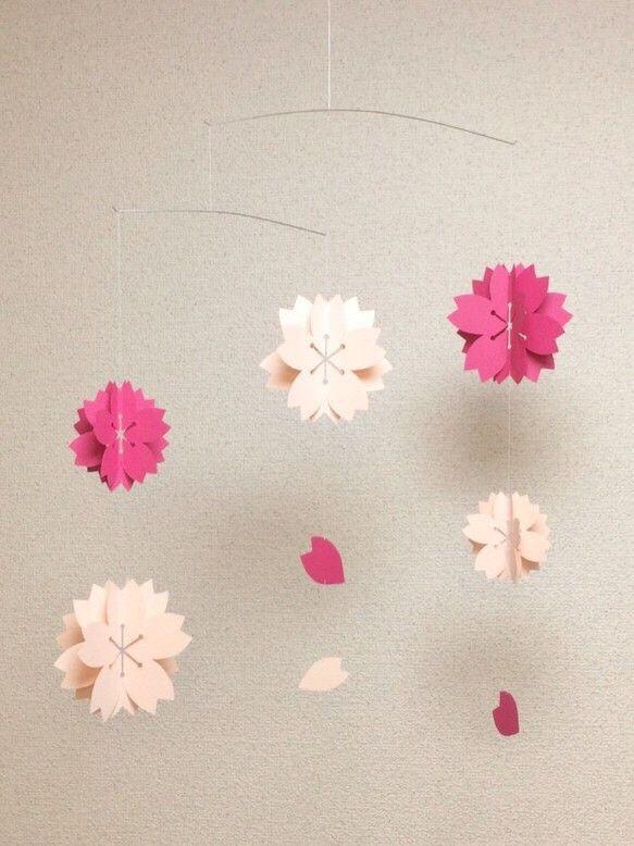 """『ハンドメイド桜2016』八重桜をイメージしました。三枚の紙を重ねたオーナメントは、立体になるように折り曲げると、華やかに、そしてボリューム感が出ます。花びらのオーナメントで散る姿を。ピンクの濃淡で優しく綺麗なモビールに仕上がりました。季節のモビールとしていかがでしょうか。☆受注後の制作にさせて頂いています。 1週間程度お時間をください。デザインから仕上げまで全て手作りです。手作りならではの """"あたたかみ"""" を感じていただけたら幸いです。空気や人の動きでゆらゆら。モビールのある生活を楽しんでください♪※1つ1つ手作りですので、形等、若干異なる場合もあります。【素材】 紙、糸、バネ線【大きさ】縦 約50㎝ × 横 約43㎝※定形外郵便:追跡(無)、補償(無) レターパックライト:追跡(有)、補償(無)"""