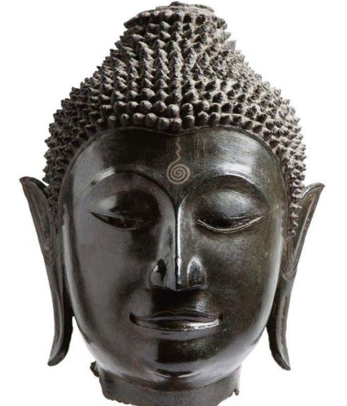 Exceptionnelle tête de Bouddha en bronze de belle patine brune, les yeux mi-clos exprimant la sérénité, les lèvres esquissant un léger sourire, présentant les signes de la boddhéité tels les oreilles aux longs lobes, les cheveux coiffés en boucles serrés surmontés de l'ushnisha, l'urna apparaissant sur le front sous forme d'un motif spiralé niellé. (Manque la flamme, ainsi que les yeux, originellement incrustés) H. 33 cm