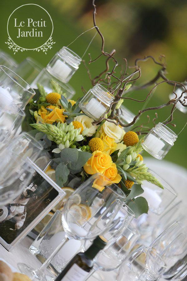 Vaso quadrato con composizione bassa realizzata con rose, berzelia, lisianthus e ornitogallo, da cui partono alti rami di nocciolo a cui vengono appese delle piccole lanterne per un effetto luccicante e molto romantico durante tutta la sera.