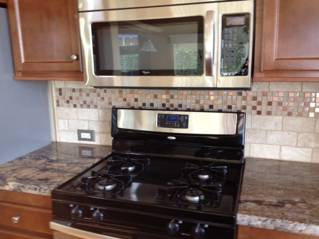 Crema Bordeaux granite countertops, black and stainless steel appliances, tumbled travertine backsplash in subway pattern with copper accent strip. In Grover Beach, California. Designed by Amber Ramirez at Natural Stone Source in Nipomo, California