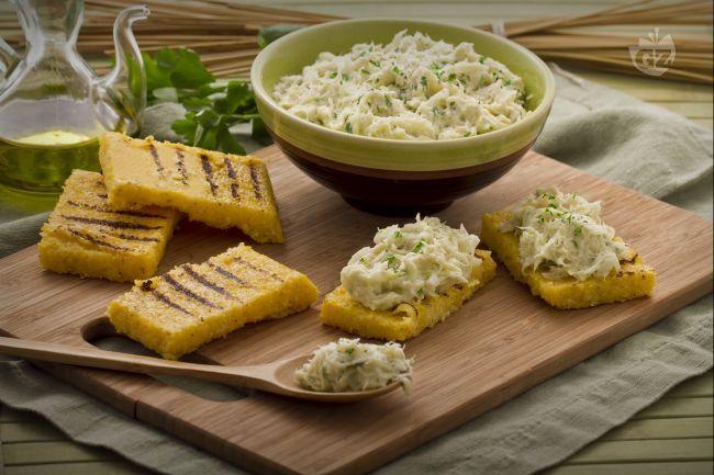 Il baccalà mantecato alla veneziana è una ricetta delicata e raffinata: una crema di baccalà condito con olio, aglio e servito con crostini di polenta