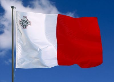 Maltese flag against blue sky. The currency used in Malta is the Euro and it is mostly a very Catholic country.
