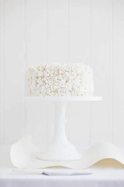 white on white, elegant texture of cake, curve of paper, lines in background create order, edge of table in photo grounds, bathed in light