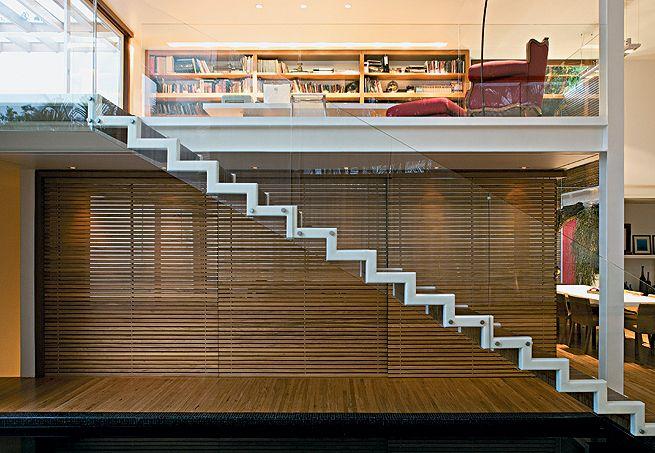 Leve e solta, a escada metálica dá acesso ao mezanino, com estrutura de vigas de aço, onde fica a biblioteca protegida por guarda-corpo de vidro temperado