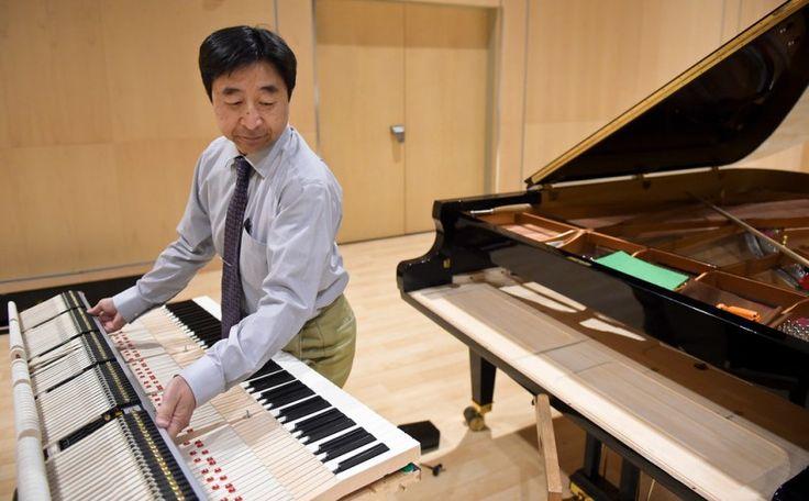 Master Piano Artisan Takanori Otake lifts the keyboard back into the Shigeru Kawai piano Wednesday at the Longmont Museum and Cultural Center.