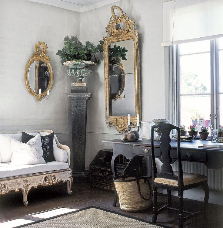 Ett rum i Gransholms herrgård med en svensk trågsoffa och en förgylld spegel på väggen.