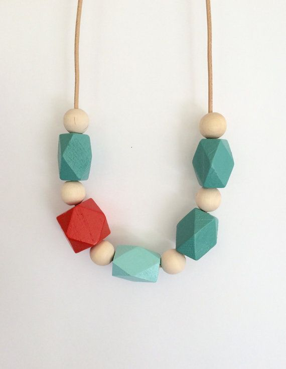 A modern array of hand painted geometric wooden beads in PEACOCK, AQUA, CORAL and RAW NATURAL WOOD. Necklace is strung on a NATURAL leather cord, and