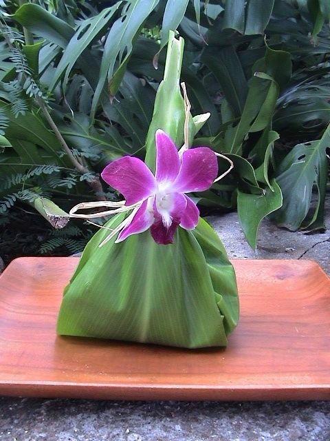 A Hawaiian snack (chocolate, macadamia nuts, cookies or jam) wrapped on a nice green leaf decorated with a gorgeous orchid or plumeria flower.
