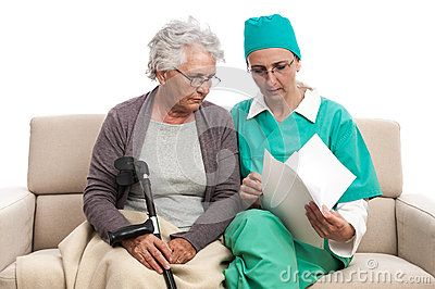 Doctor or nurse talking with disable old women and looking on papers. Female doctor helping  old disabled women at home visit. Isolated on white.