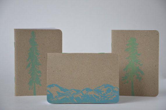 Jeder Skizzenbuch ist Handbedruckt mit einem Lino-Block. Bilder auf die Skizzenbücher variieren von Bäumen zu Kameras. Skizzenbücher haben leere Seiten und sind 3,5 x 4 in der Größe. Ein gemeinsames Projekt mit Scout Bücher
