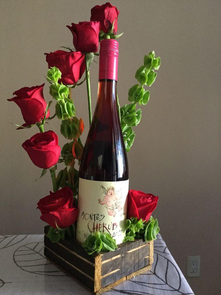 Arreglo floral con botella de vino, rosas rojas con campana.