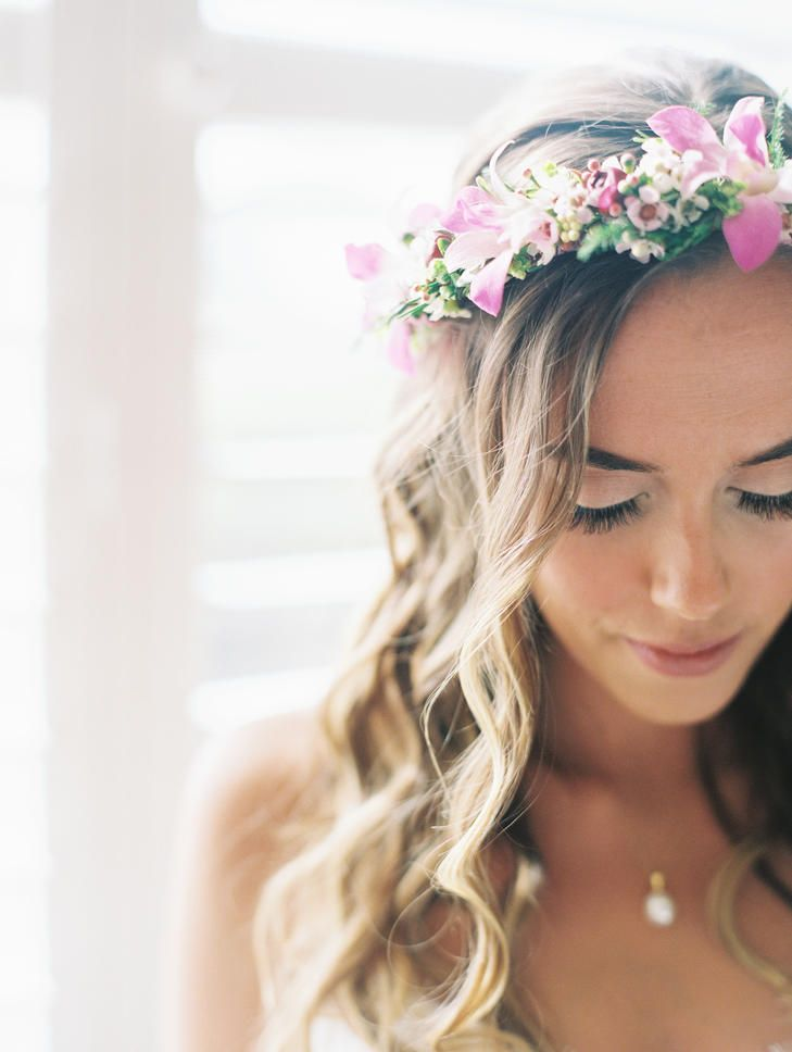 Loose curls paired with a traditional Hawaiian bridal crown, called a haku, made up of greenery and pink blossom