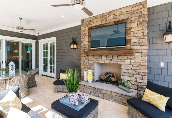 Outdoor patio fireplace. The patios has a fireplace with a reclaimed wood accent wall above the reclaimed wood mantel. #outdoor #fireplace #stonefireplace #reclaimedwoodmantel