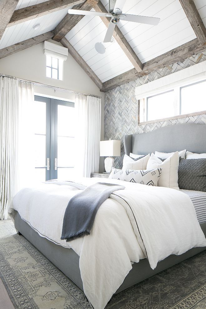 The gray, white, and navy tones in this master bedroom are breathtaking!