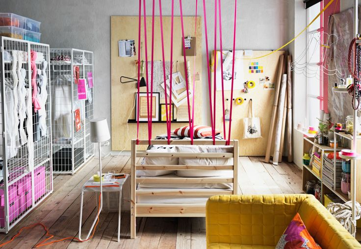 A modern bedroom with pink ropes making a headboard for a wooden single bed surrounded by wood walls and modern style storage