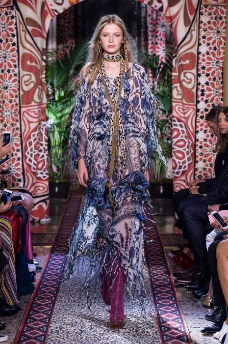 La modella indossa un abito a balze trasparente in chiffon, con le frange e in stile vittoriano, abbinato a stivali viola scamosciati.