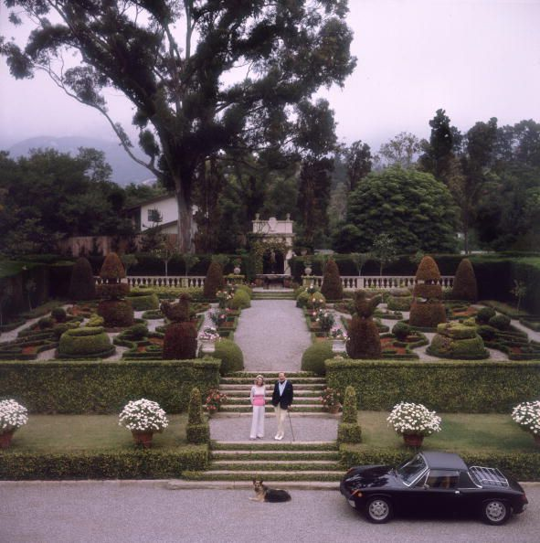 Circa 1970, Mr. and Mrs. J Gordon Douglas in the formal gardens of their residence, Santa Barbara, California, USA. (Photo by Slim Aarons/Getty Images)