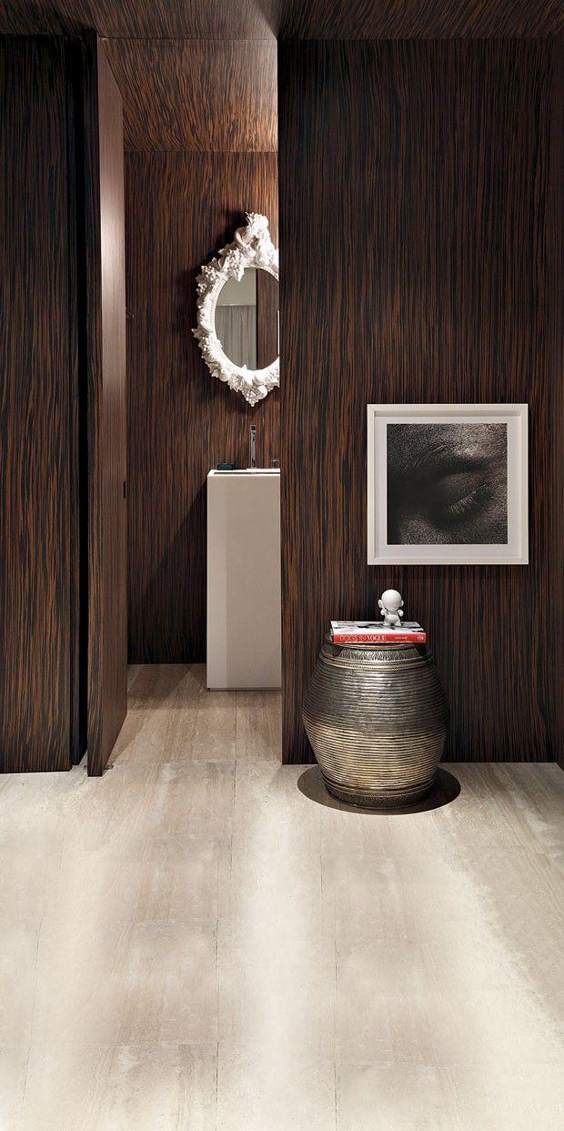 Caixa de ébano. Na reforma do apartamento em Curitiba, lavabo do arquiteto Guilherme Torres. A alvenaria foi substituída por uma estrutura de MDF revestida com ébano-de-macassar. A cor escura se contrapõe ao mármore travertino do piso e ao Corian branco d