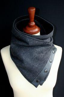 Mooie zwarte sjaal waarvan de buitenkant van een donker- met lichtgrijs gestreepte (vissengraad motief) stof is en de binnenkant is van een zachte zwarte fleece. Aan de uiteinden zit een zwart kunstleer waar zwarte drukknopen op bevestigd zitten. Met deze drukknopen en twee extra drukknopen aan beide zijkanten kun je de sjaal op heel veel verschillende manieren dragen, voor zowel binnen als buiten.