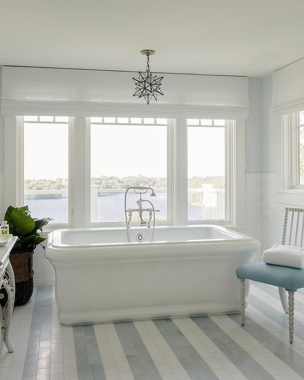 Enjoy the view of the beach, while you bathe in a rectangular freestanding tub placed on white and blue striped floor tiles in front of a window dressed in a white roman shade illuminated by the Moravian Star Pendant hung over the tub as a white spindle chair with a blue cushion sits beside it.