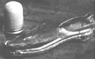 """This tiny shoe was found in 1835 by a farmer on a remote sheep trail on the Beara Peninsula in Ireland. It measures 2&7/8"""" long and 7/8"""" at its widest.It is black and shows wear at the heel. The farmer gave the shoe to the local doctor, and eventually it was passed to the Somerville family. It was reportedly examined by scientitsts at Harvard University and found to have tiny hand stitches, well-crafted eyelets, and appeared to be made of mouse skin.  Makes you think doesnt it!"""