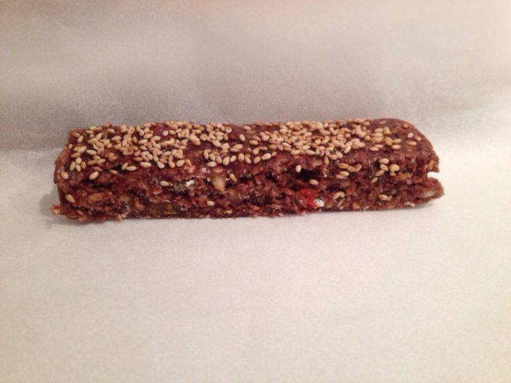 Zelfgemaakte proteinbars met chocolade eiwitpoeder, pindakaas, diverse noten en goji bessen. Getopt met sesamzaadjes