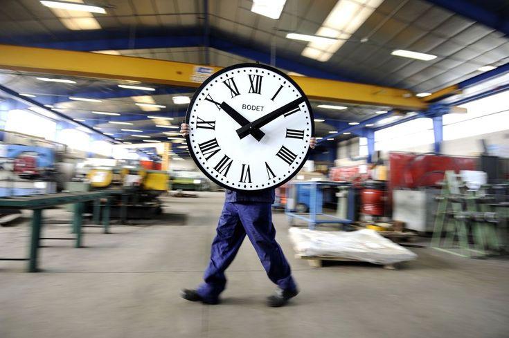 Un empleado de la compañía Bodet transporta un reloj en la plaza de Trementines (Francia).