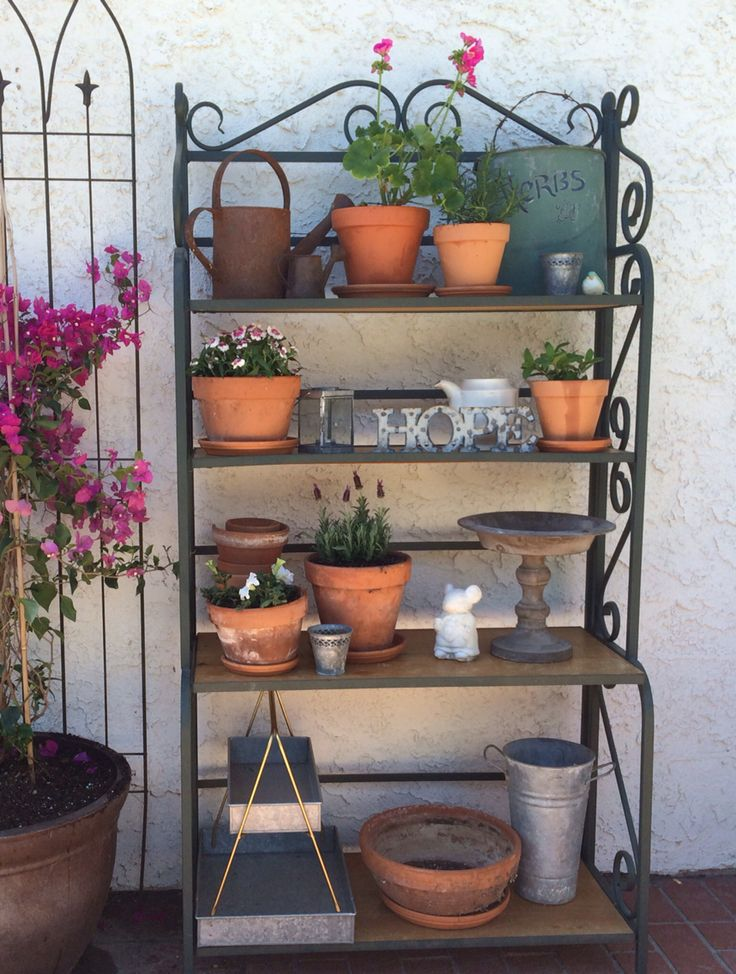 Repurposed bakers rack. This turned into a great garden shelf using simple terra cotta pots and galvanized metal.