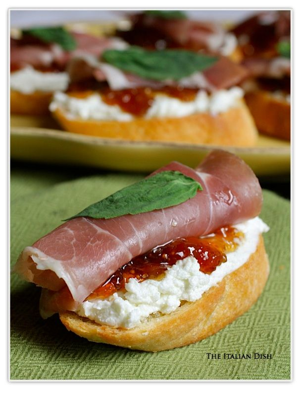 Crostini topped with goat cheese, fig jam, prosciutto and a fresh basil leaf...