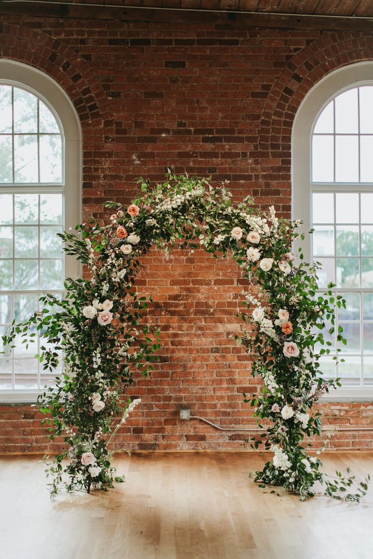 Ceremony backdrop arch with flowers and greenery. Warehouse wedding in Durham, NC. Photography: Brian Schindler Co. www.brianschindlerphotography.com Flowers: Meristem Floral www.meristemfloral.com #flowers #wedding #ceremony #backdrop #arch #installation #arbor