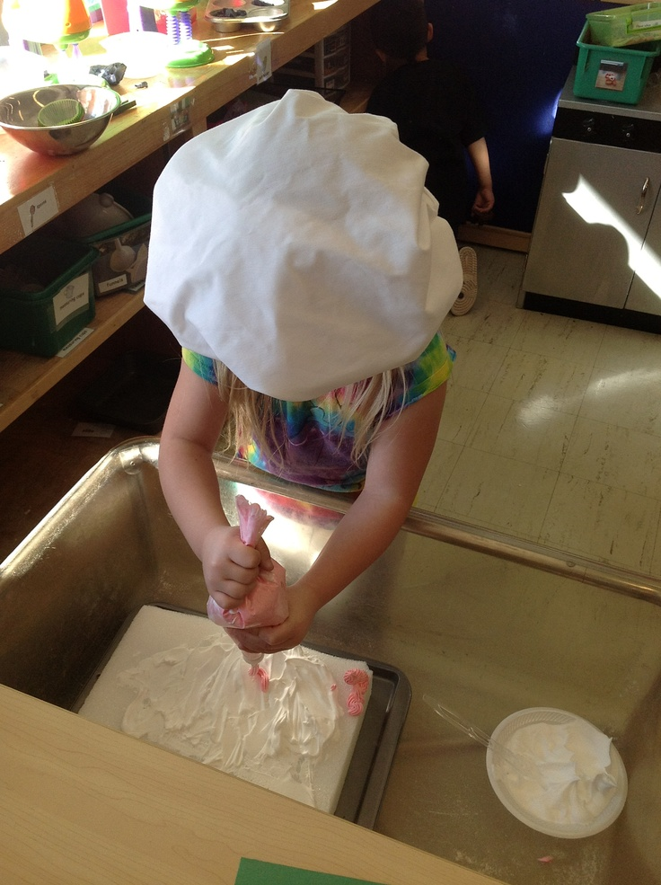 "Cake decorating at Bakery. Colored shaving cream for frosting and real decoraters tips and bags. Styrofoam ""cake"""