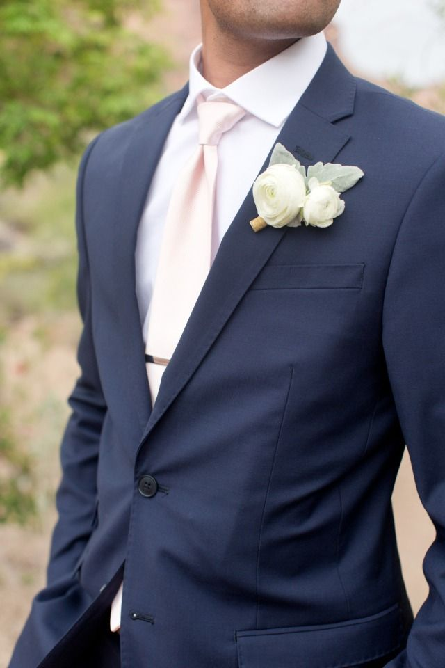 groom in navy suit with blush tie and white boutonniere