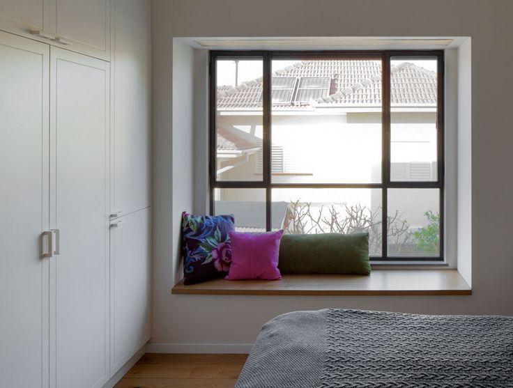 בחדר ההורים תוכנן לצד המיטה אדן חלון רחב, שעליו הונח משטח עץ אלון עם כריות נוי ( צילום: אלעד שריג )
