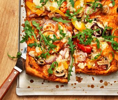 Med detta recept fixar du en knaprig och spännande hemmagjord pizza. På pizzan lägger du rödlök, paprika, champinjoner, fetaost, pizzaost och ruccola. Pizza med paprika och feta är en utmärkt rätt till fredagsmyset.