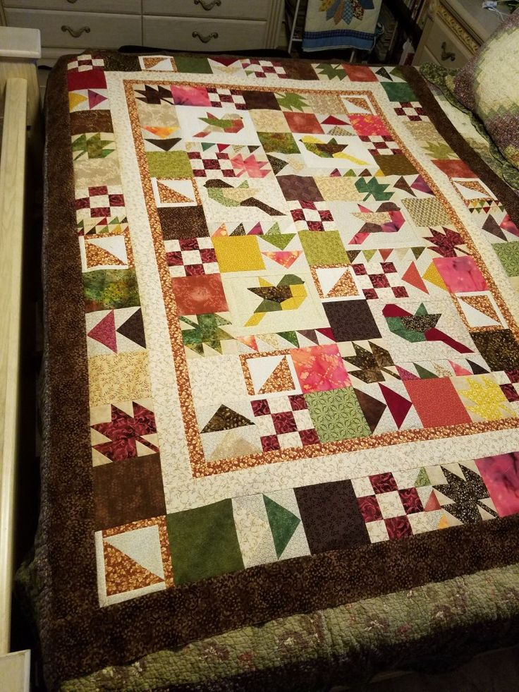 "Fall Jumble quilt. It started with the birds. My niece suggested the leaves. The other blocks just seemed to fit. The solid blocks are ""a place for the eyes to rest""."