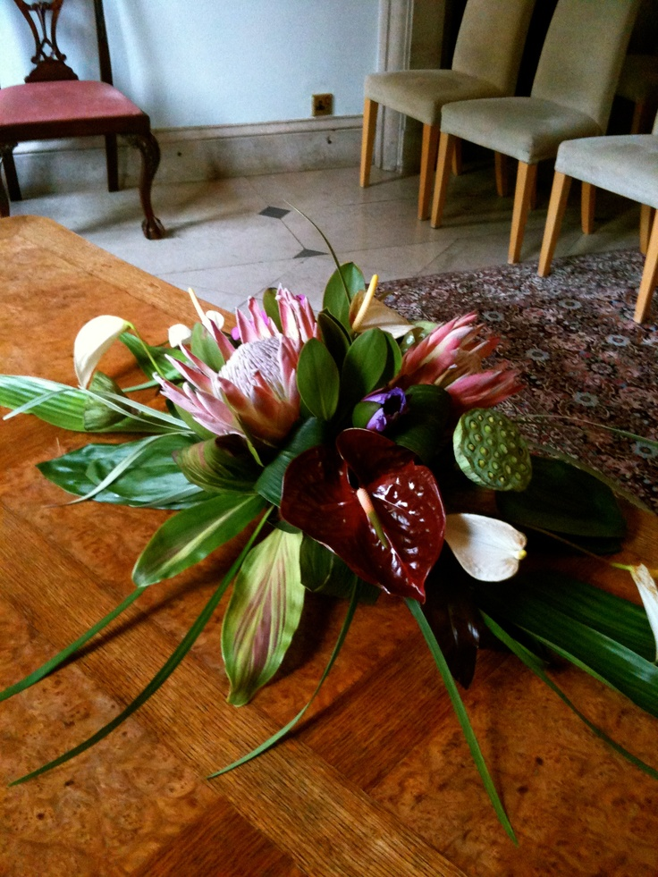 Tropical set arrangements of King Proteas, Chocco Anthurius, Lotus Head and Flowers, with tropical foliages.